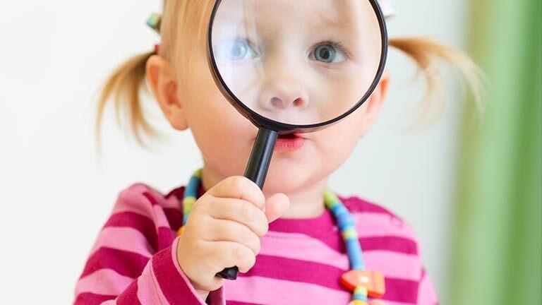 tyttö katsoo suurennuslasin läpi