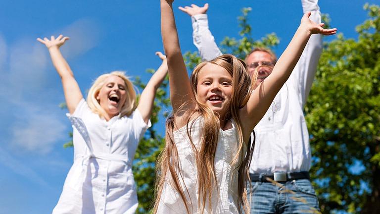 perhe hyppää kädet ylhäällä ilmaan