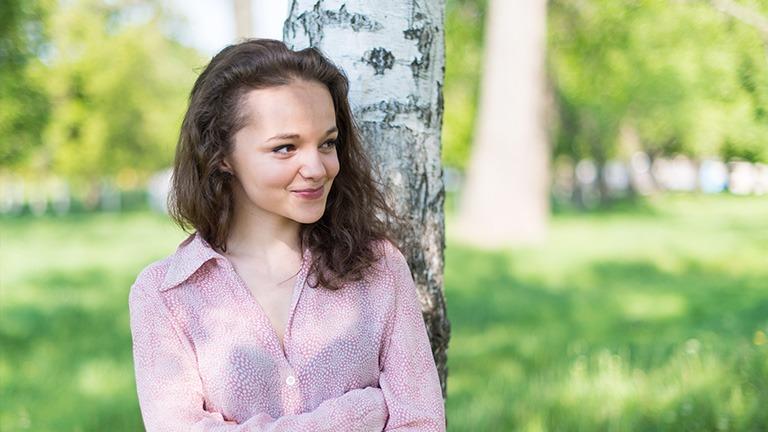 teini-ikäinen tyttö njaa puuhun ja hymyilee