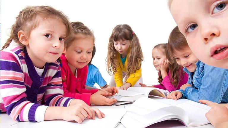 lapsia pöydän ääressä kirjoja auki pöydällä