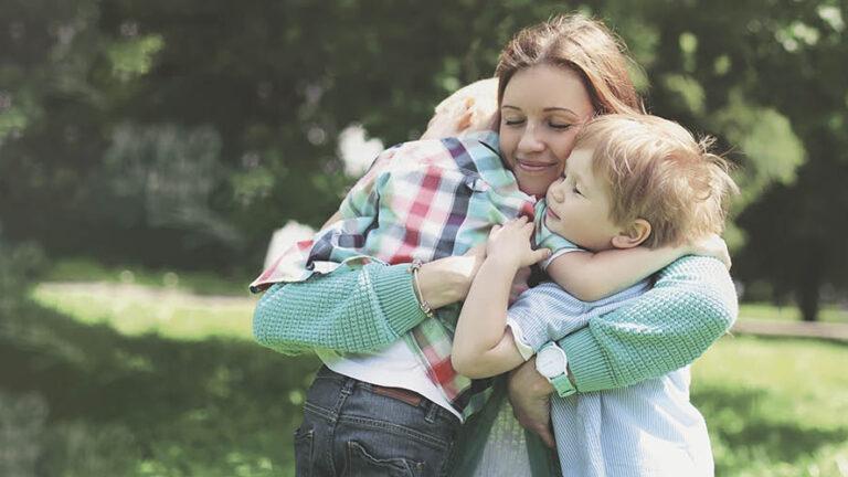 Äiti halaa lapsiaan puistossa.