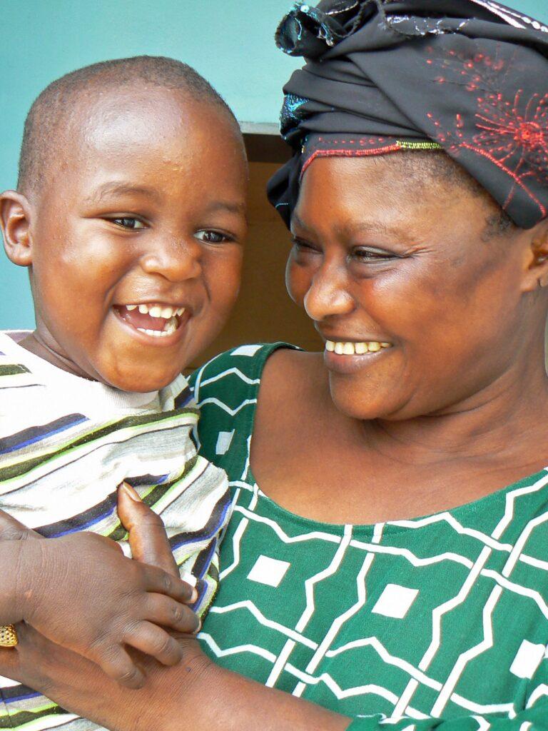 Afrikkalainen äiti pistää lasta sylissä ja molemmat ovat hymyissä suin.