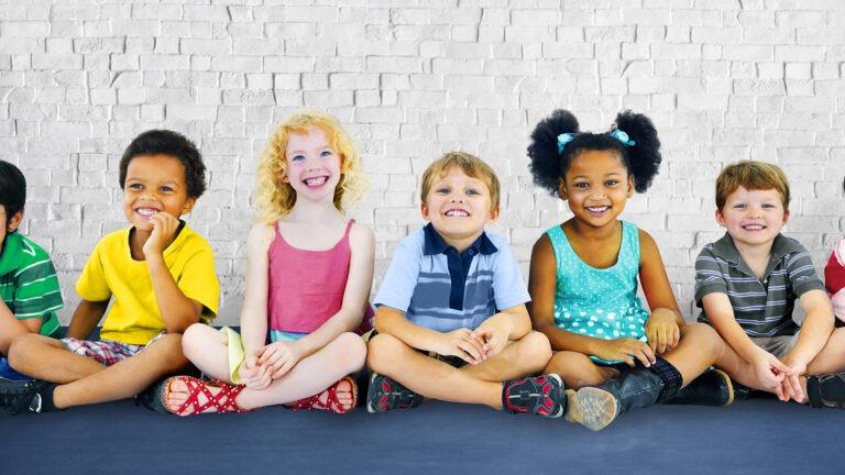 lapset istuvat hymyillen rivissä