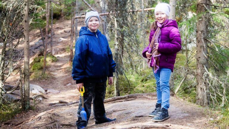 Kaksi lasta seisoo metsässä kallion päällä