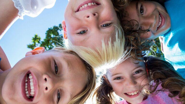 Lähikuva lasten nauravista kasvoista