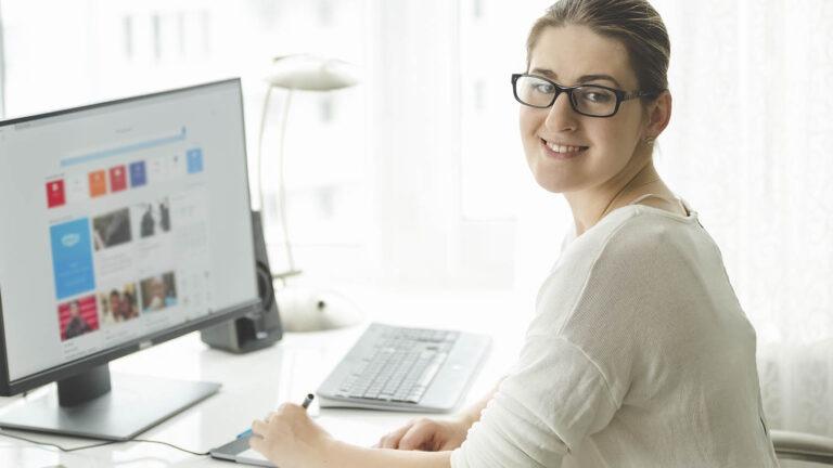 nainen hymyile tietokoneen ääressä kameralle, ekumppani
