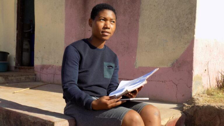 Themba kotinsa edutalla istumassa rappusilla
