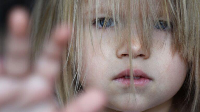Surullinen lapsi ikkunassa