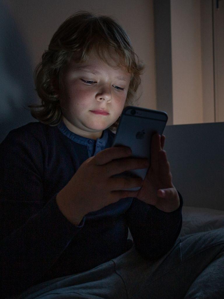 Pieni poika katselee kännykkää pimeässä huoneessa.