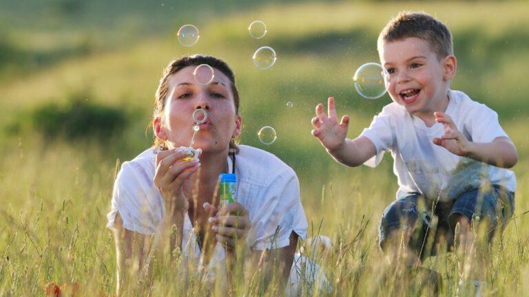Nainen puhaltaa saippuakuplia niityllä pienen pojan kanssa