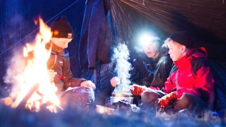 Partiolaiset telttailemassa lumen keskellä hämärässä