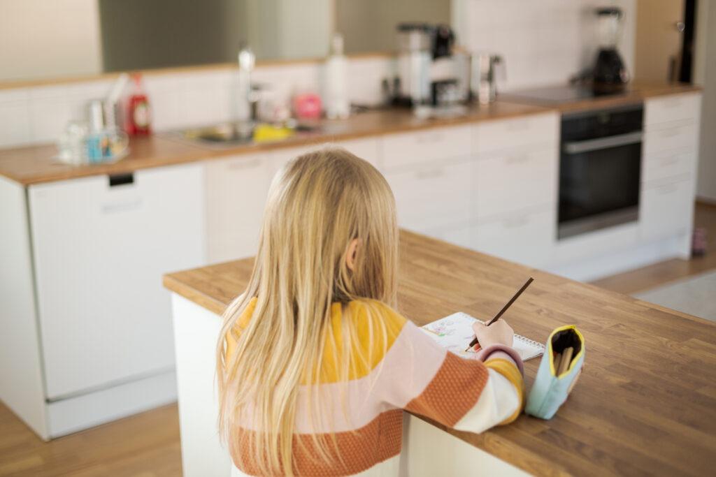 vaaleahiuksinen tyttö kuvattuna takaapäin, piirtää keittiön tason päällä