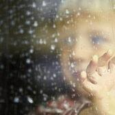 lapsi ikkunan takana, lasissa pisaroita