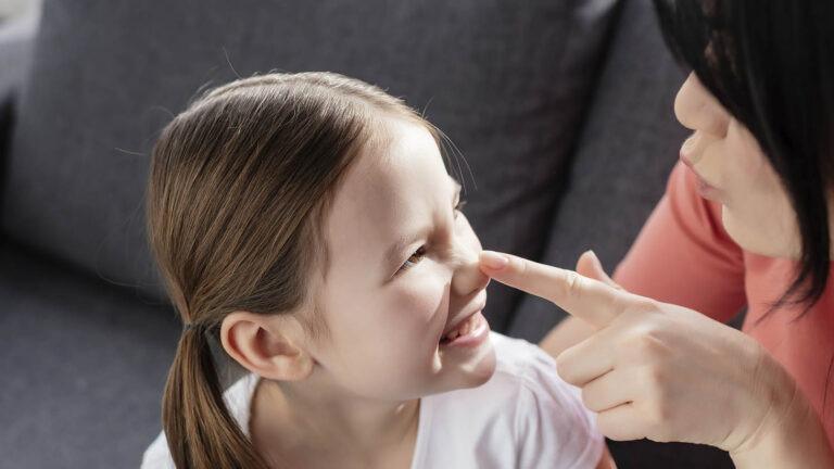tummahiuksinen naoinen koskettaa nuoren tytön nenää istuen sohvalla