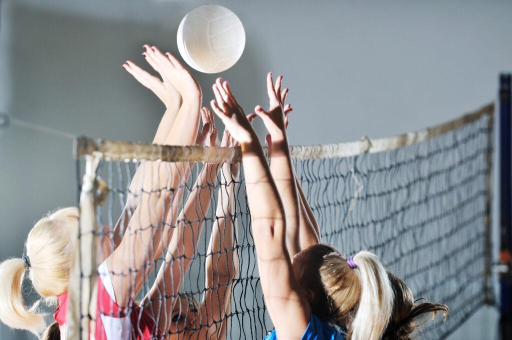 tyttöjä pelaamassa lentopalloa
