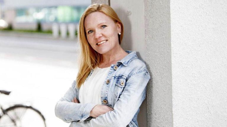 hymyilevä nainen katsoo kameraan ja nojaa vaaleaan talon seinään ulkona