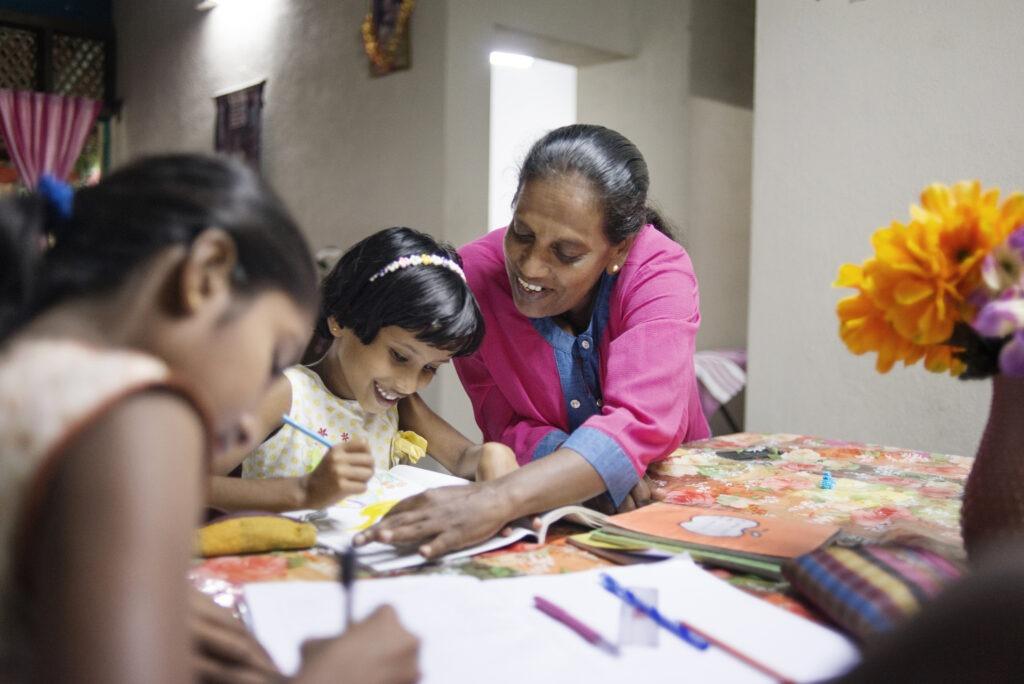 lapsikylä-äiti auttaa lapsia kotitehtävissä