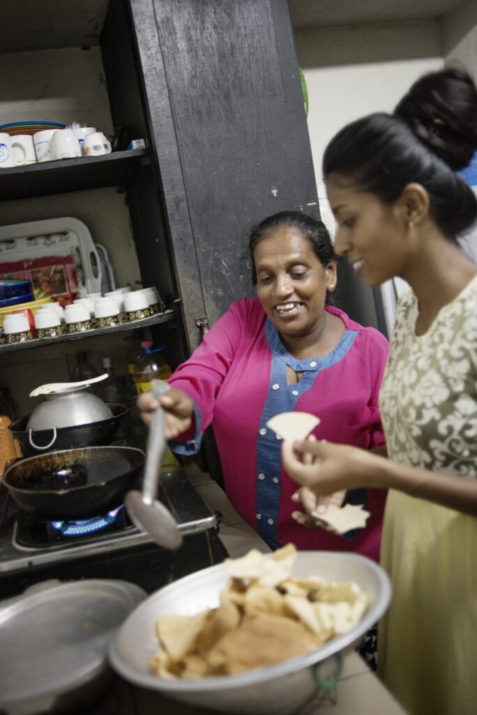 lapsikylä-äiti ja perheen isoin tyttö tekevät yhdessä ruokaa keittiössä