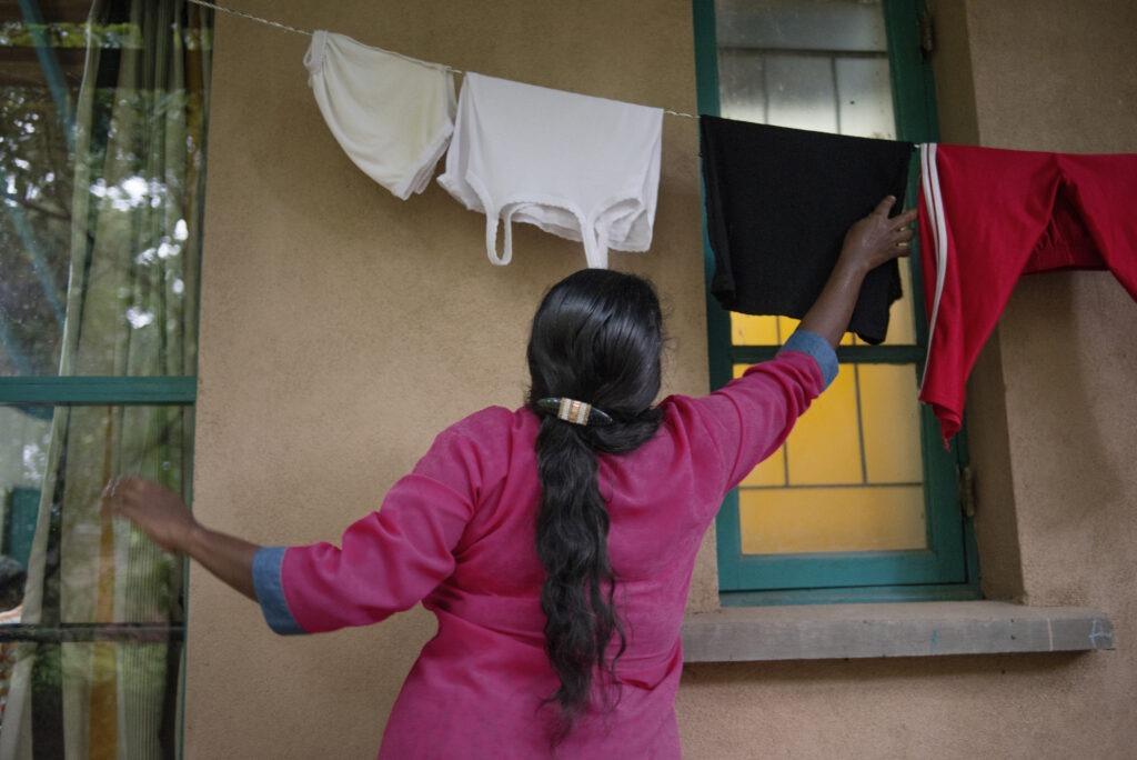 Malani lapsikylä-äiti ripustaa pyykkeijä kuivumaan talon ulkopuolella