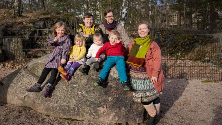 suurperheestä kuva istumassa isolla kivellä puistossa