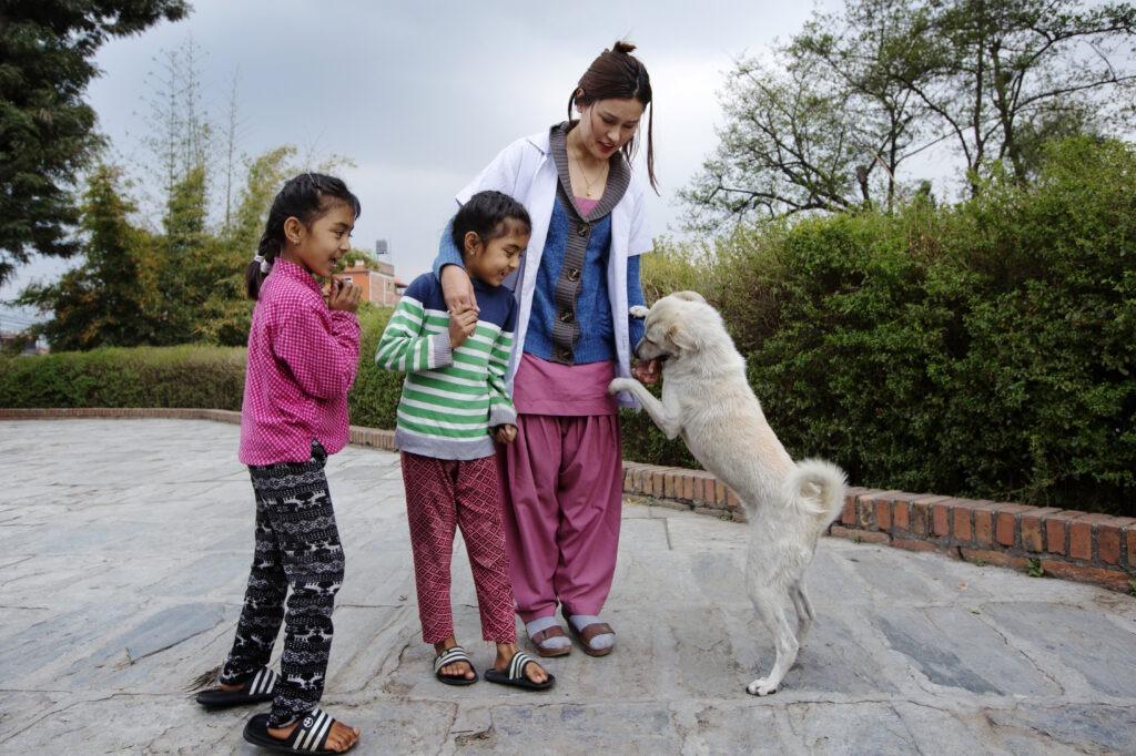 sairaanhoitaja, kaksi lasta ja koira pihalla