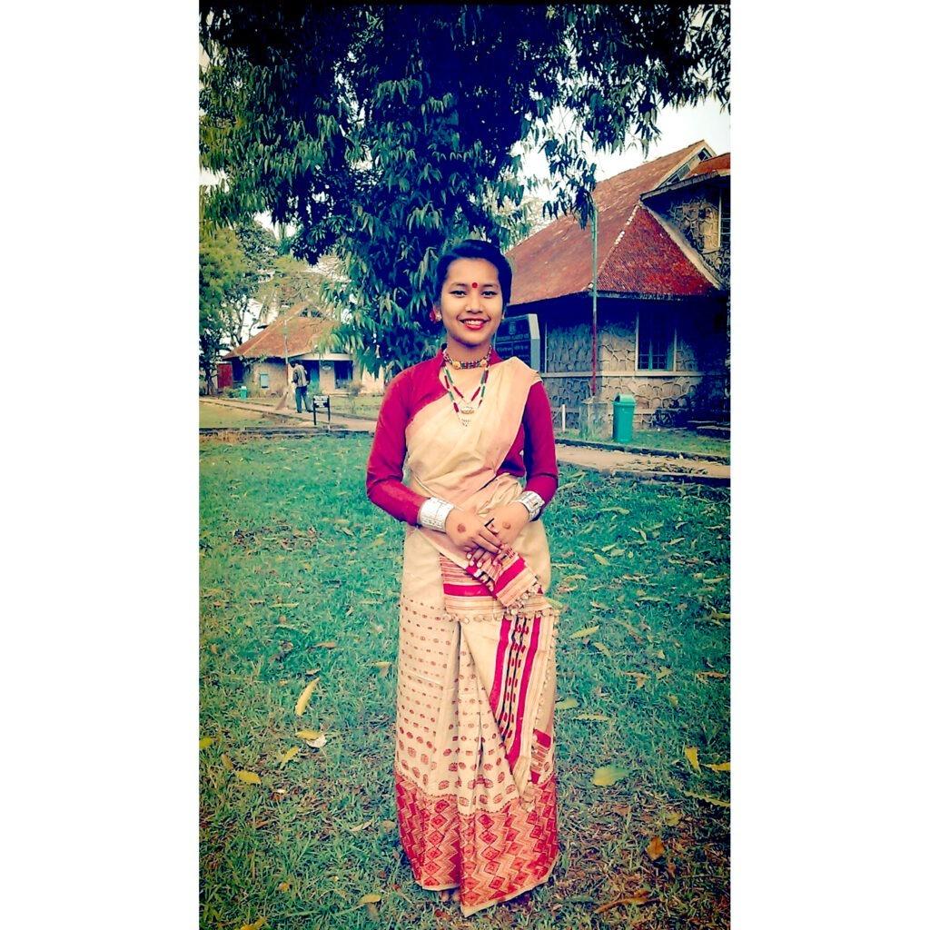 Intialainen nainen kansallispuvussa ruohikolla tiilitalon edustalla