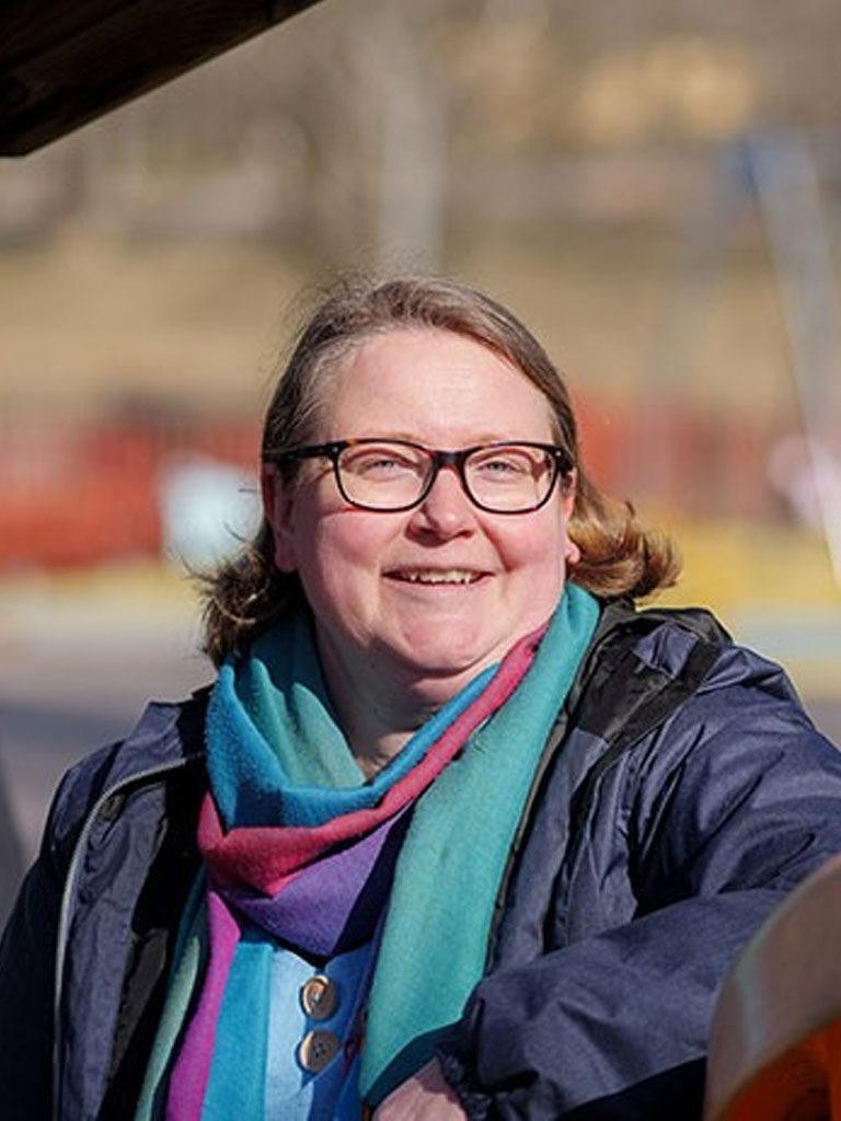 hymyilevä silmälasipäinen ruskeahiuksinen nainen ulkona auringonpaisteessa