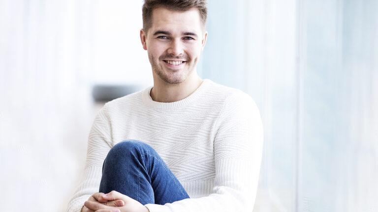 ruskeahiuksinen mies hymyilee ja katsoo kameraan, valkoinen paita ja siniset farkut jalassa