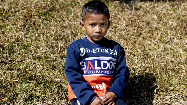 poika istuu kuivuneella nurmikolla