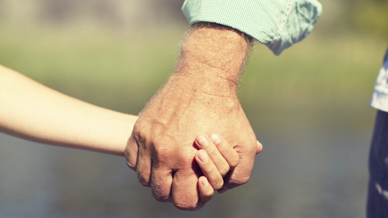 Vanhan miehen käsi pitää lapsen kädestä kiinni