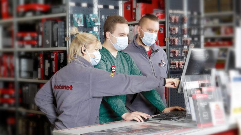 motonetin kaupassa kaksi työntekijää neuvoo nuosta kassan käytössä