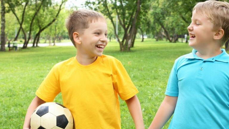 Kaksi poikaa seisovat käsi kädessä, yhdellä on jalkapallo